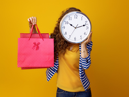 young woman with long wavy brunette hair isolated on yellow holding clock in the front of face and showing shopping bags