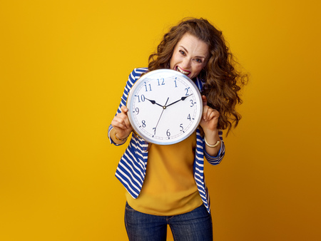 stressed stylish woman with long wavy brunette hair against yellow background biting clock Stock Photo