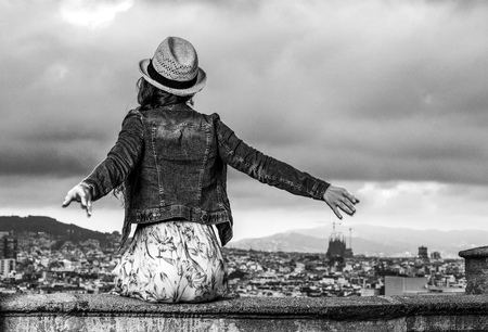 Perfect evening with stunning view. Seen from behind young traveller woman in long dress and straw hat in the front of cityscape of Barcelona, Spain relaxing