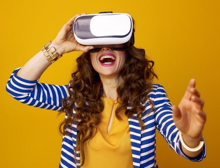 Portrait of happy young woman with long wavy brunette hair isolated on yellow background wearing VR headset Stok Fotoğraf