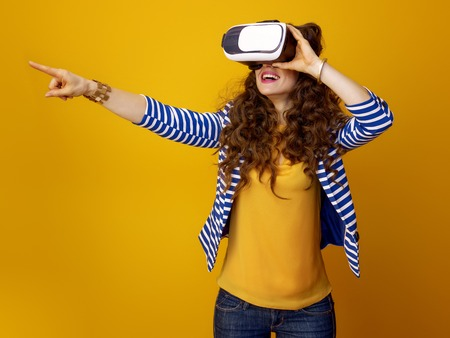 happy young woman with long wavy brunette hair isolated on yellow background wearing VR headset and pointing at something