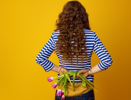 Seen from behind trendy woman with long wavy brunette hair against yellow background holding wilted flowers Stock Photo