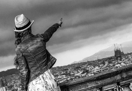 Perfect evening with stunning view. Seen from behind modern tourist woman in long dress and straw hat in the front of cityscape of Barcelona, Spain pointing at something Stock Photo