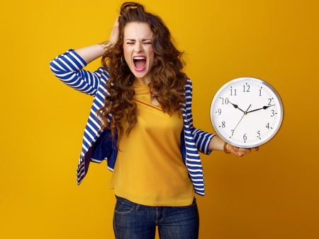 stressed young woman with long wavy brunette hair on yellow background with clock
