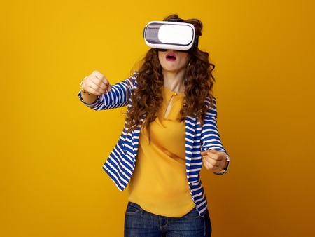 surprised young woman with long wavy brunette hair on yellow background using VR headset and driving