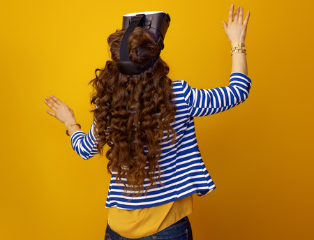 Seen from behind trendy woman in striped jacket on yellow background using VR headset Stok Fotoğraf - 97384350