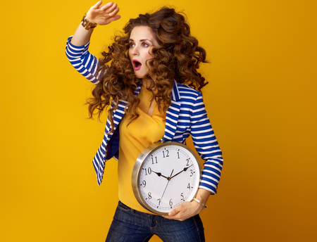 surprised stylish woman in striped jacket isolated on yellow background with clock looking into the distance