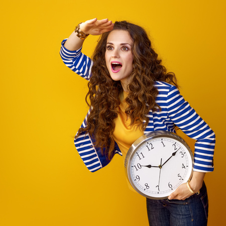 surprised modern woman in striped jacket against yellow background with clock looking into the distance