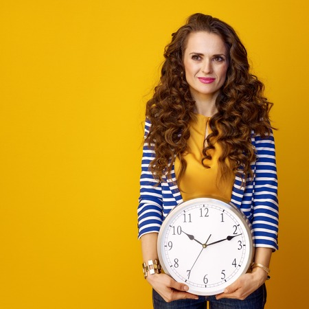 young woman in striped jacket on yellow background with clock