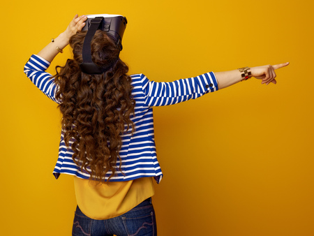 Seen from behind trendy woman with long wavy brunette hair isolated on yellow background in VR headset pointing at something Stok Fotoğraf - 97384357