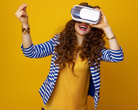 happy stylish woman with long wavy brunette hair against yellow background using virtual reality gear and snapping fingers