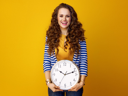 smiling stylish woman with long wavy brunette hair against yellow background with clock Stock Photo