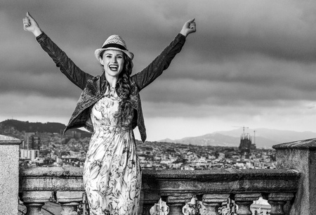 Perfect evening with stunning view. happy stylish woman in long dress and straw hat in the front of cityscape of Barcelona, Spain rejoicing