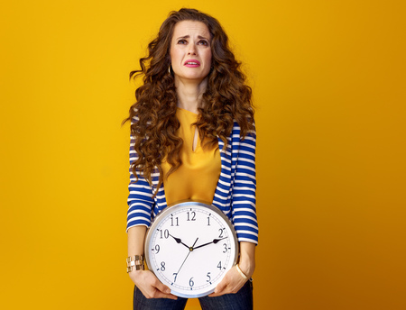 unhappy trendy woman in striped jacket isolated on yellow with clock Banco de Imagens