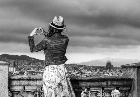 Perfect evening with stunning view. Seen from behind elegant traveller woman in long dress and straw hat in Barcelona, Spain showing heart shaped hands