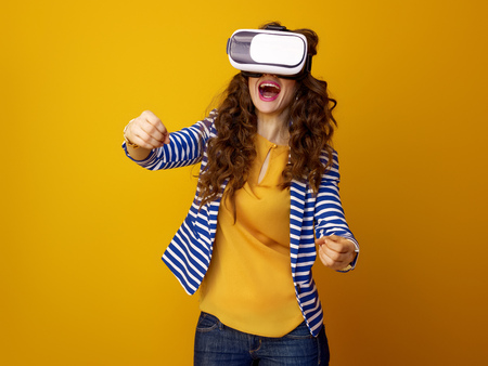 smiling stylish woman with long wavy brunette hair isolated on yellow wearing cardboard VR glasses and driving Stockfoto