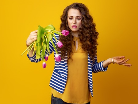 indignant young woman with long wavy brunette hair isolated on yellow indignant with wilted flowers 写真素材 - 97384701