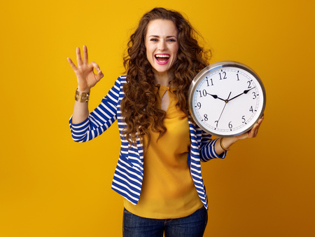 smiling trendy woman in striped jacket isolated on yellow background with clock showing ok gesture