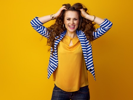 Portrait of cheerful modern woman in striped jacket on yellow background Stock fotó
