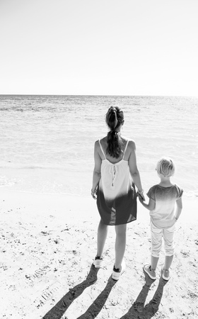 Colorful and wonderfully cheerful mood. Seen from behind modern mother and daughter in colorful clothes on the seacoast looking into the distance Stock Photo