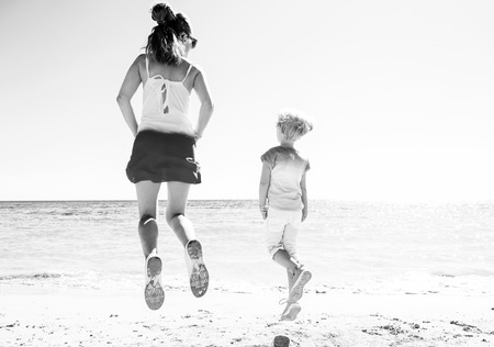 Colorful and wonderfully cheerful mood. Seen from behind modern mother and child in colorful clothes on the beach jumping