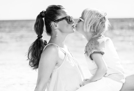 Colorful and wonderfully cheerful mood. trendy mother and daughter in colorful clothes on the seashore kissing