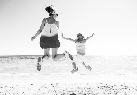 Colorful and wonderfully cheerful mood. Seen from behind trendy mother and daughter in colorful clothes on the seacoast jumping