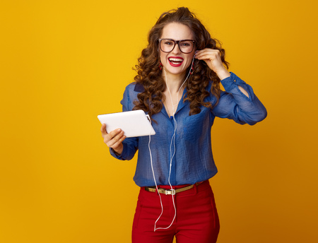 smiling modern woman with long wavy brunette hair with tablet PC listening to the music with headphones isolated on yellow