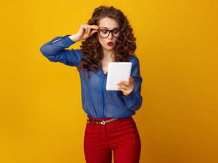 surprised stylish woman with long wavy brunette hair with tablet PC isolated on yellow