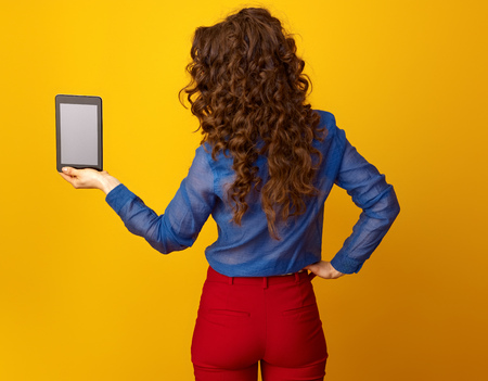 Seen from behind trendy woman with long wavy brunette hair showing tablet PC blank screen on yellow background