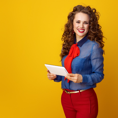 smiling trendy woman with long wavy brunette hair with tablet PC on yellow background