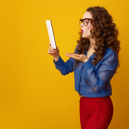 young woman with long wavy brunette hair with tablet PC blowing air kiss against yellow background Stock Photo