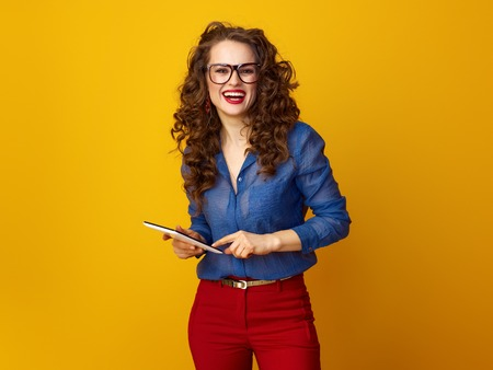 smiling modern woman with long wavy brunette hair using tablet PC against yellow background