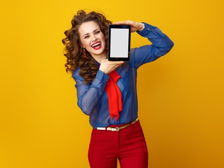 happy modern woman with long wavy brunette hair against yellow background showing tablet PC blank screen Stock Photo