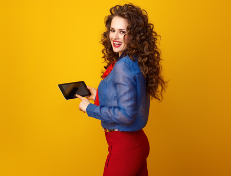 happy young woman with long wavy brunette hair using tablet PC on yellow background