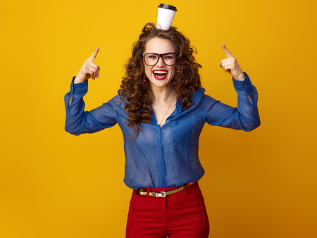 happy young woman with long wavy brunette hair pointing at coffee cup on head isolated on yellow Foto de archivo - 97946735