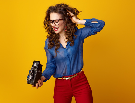 happy trendy woman with long wavy brunette hair using retro photo camera isolated on yellow background Stock Photo