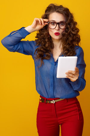 surprised young woman with long wavy brunette hair with tablet PC isolated on yellow background Stock Photo