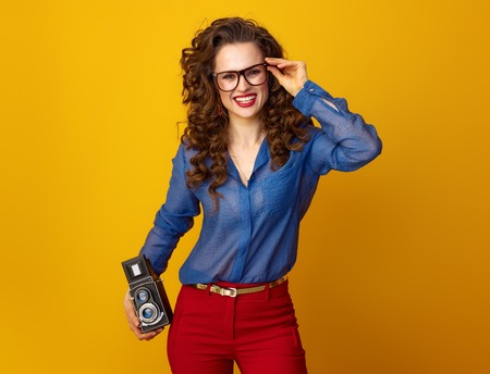 Portrait of happy trendy woman with long wavy brunette hair with retro photo camera isolated on yellow background 版權商用圖片