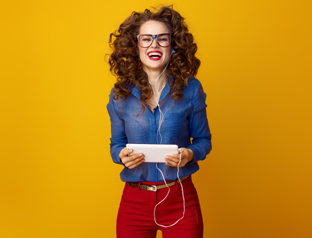 happy trendy woman with long wavy brunette hair with tablet PC listening to the music isolated on yellow