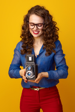 smiling trendy woman with long wavy brunette hair using retro photo camera isolated on yellow background