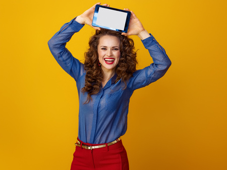smiling young woman with long wavy brunette hair showing tablet PC blank screen isolated on yellow Фото со стока