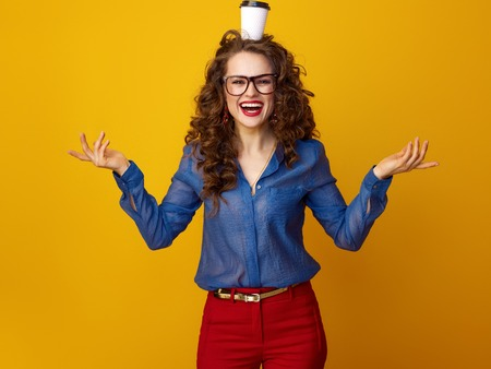 smiling modern woman with long wavy brunette hair with a coffee cup on head isolated on yellow Foto de archivo - 97988880