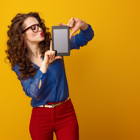 modern woman with long wavy brunette hair showing tablet PC blank screen isolated on yellow background