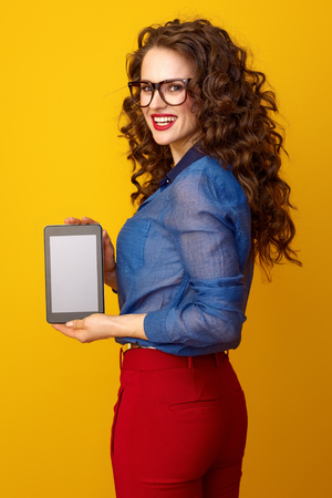 happy young woman with long wavy brunette hair showing tablet PC blank screen isolated on yellow background Stock Photo