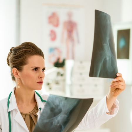 Medical doctor woman looking on fluorography in office