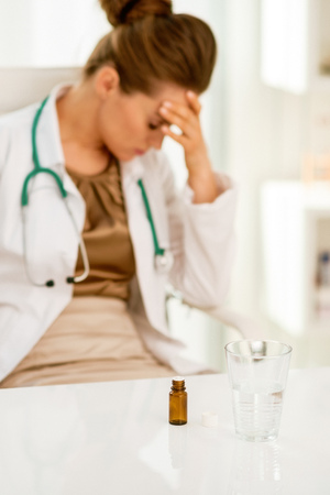 Closeup on calmative and glass stressed medical doctor woman in background