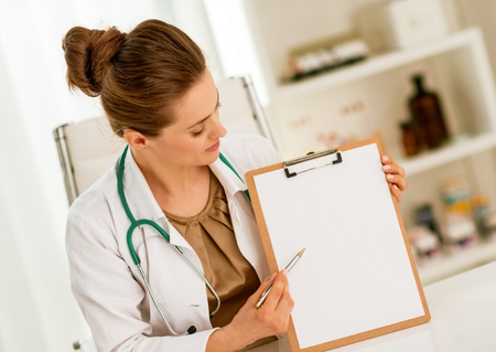 Happy medical doctor woman pointing in clipboard 스톡 콘텐츠