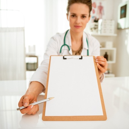 Closeup on doctor woman pointing on clipboard Stock Photo