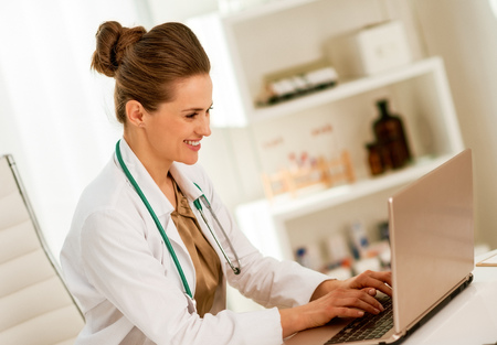 Doctor woman working on laptop in office